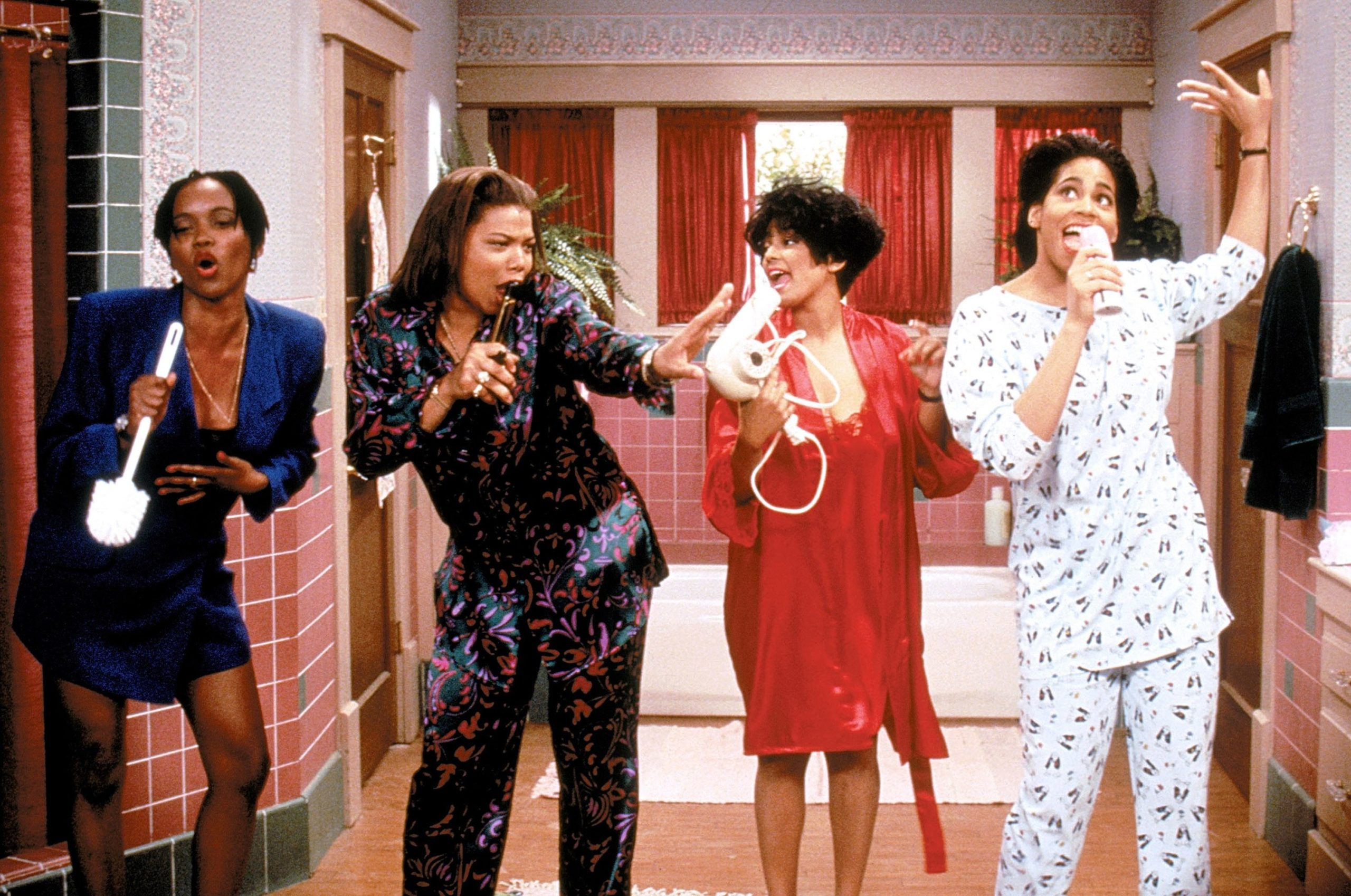 Four Black women circa the early 90's stand together dancing and singing into telephones.
