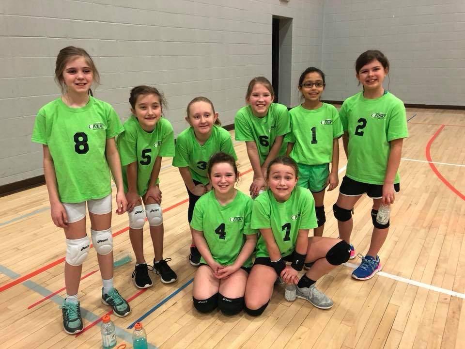 A group photo of 8 youth volleyball athletes