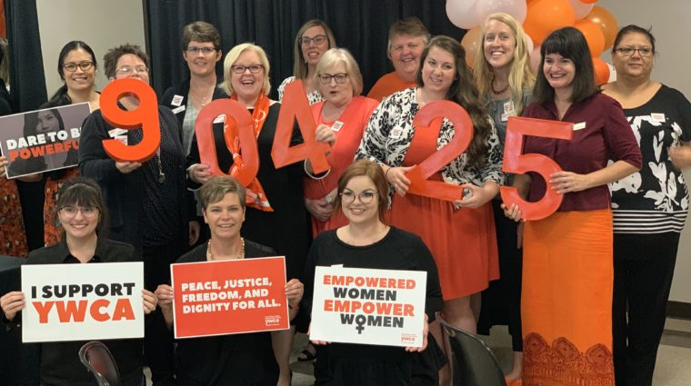 YWCA staff members posing with orange numbers