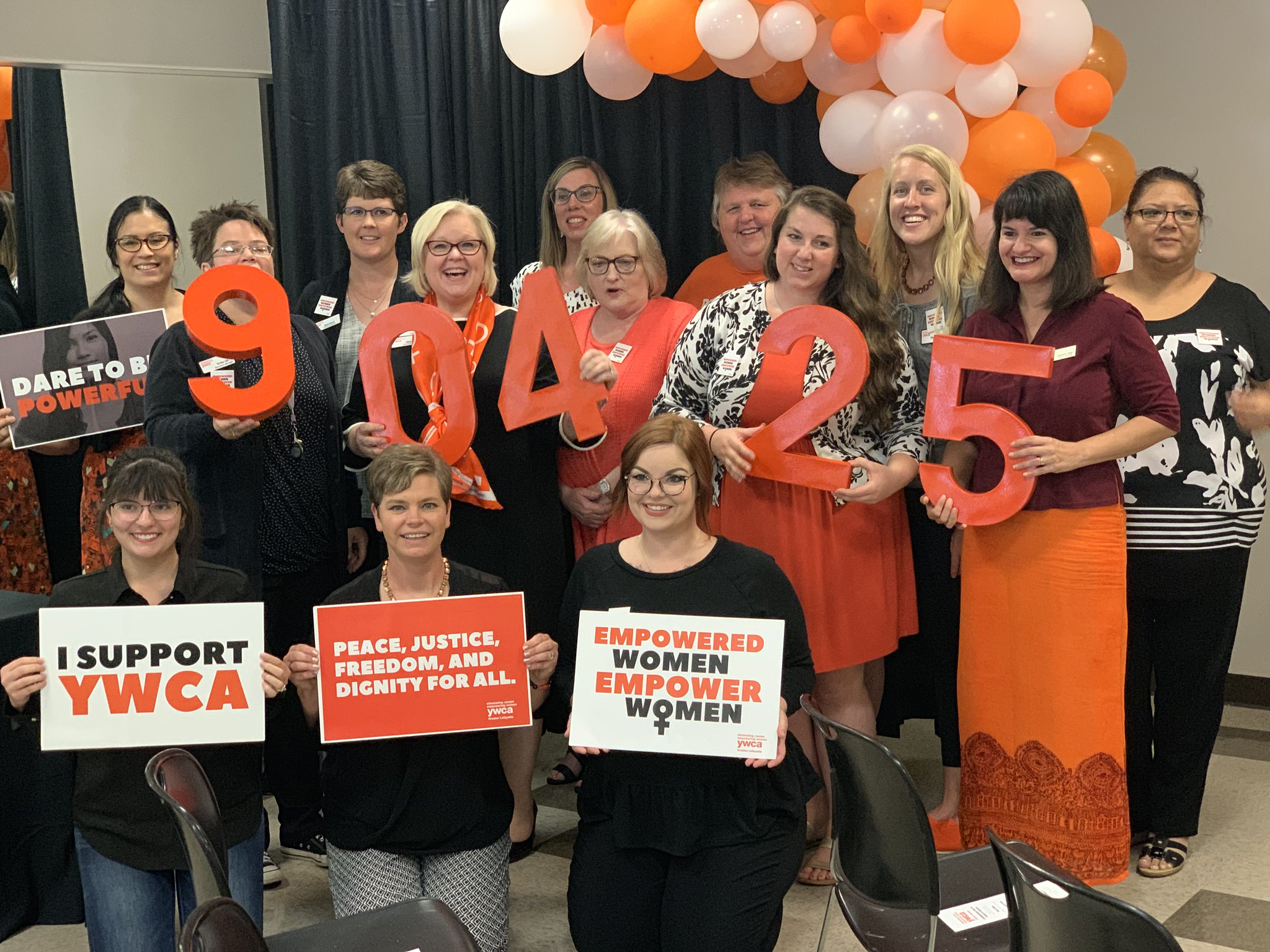 YWCA staff members posing with orange numbers