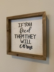 """Framed sign that reads """"If you feed them they will come"""""""