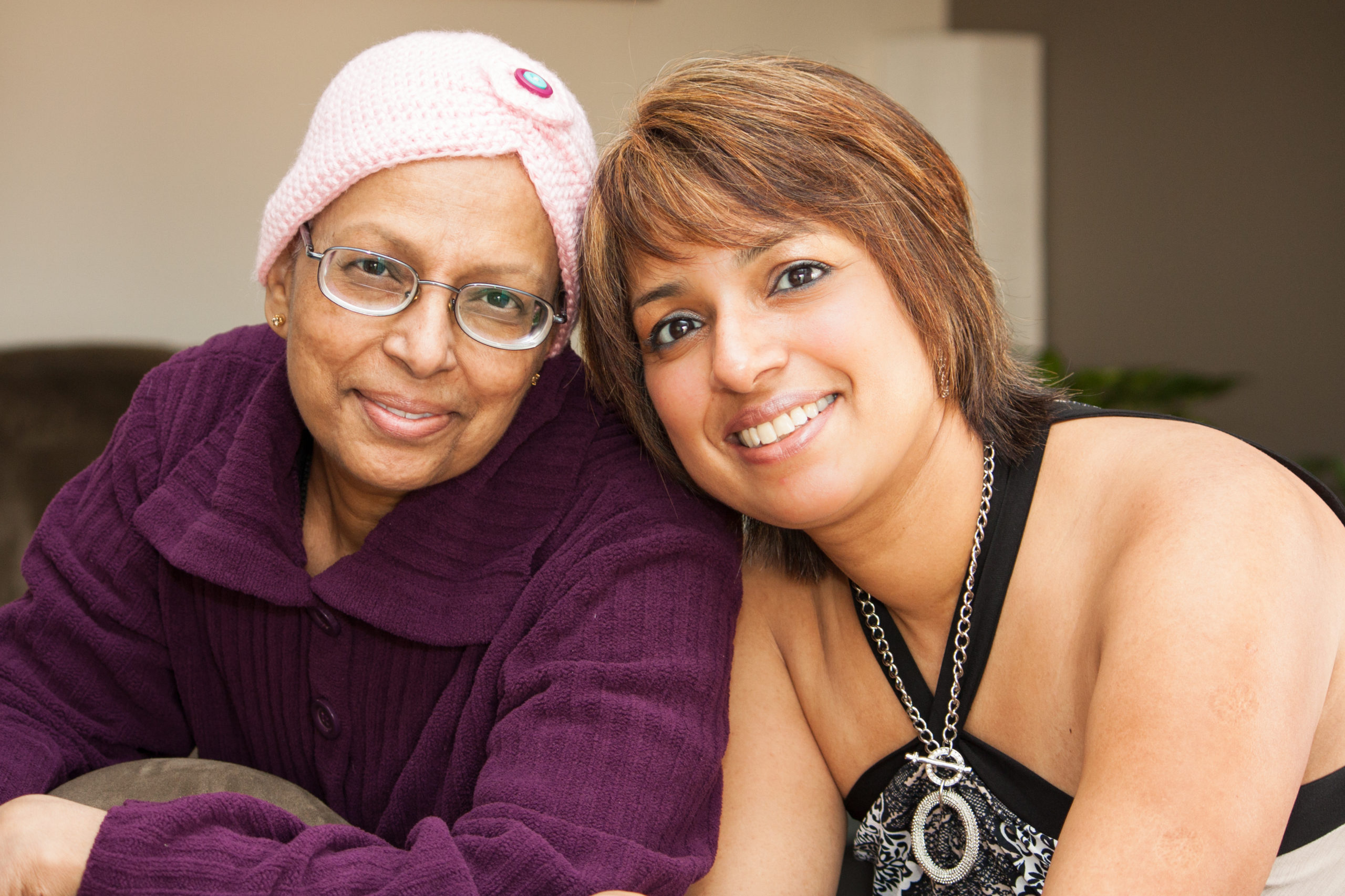 Two women are seated, smiling at a camera. The older of the two is a cancer patient. She is wearing a light pink hat.