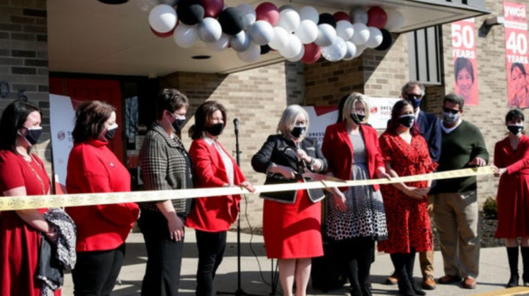 dress for success launch photo of women wearing red and black cutting a ribbon in front of YWCA
