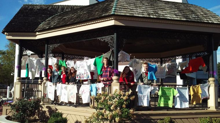 Volunteers pose with T-shirts displayed on cotheslines on a gazebo