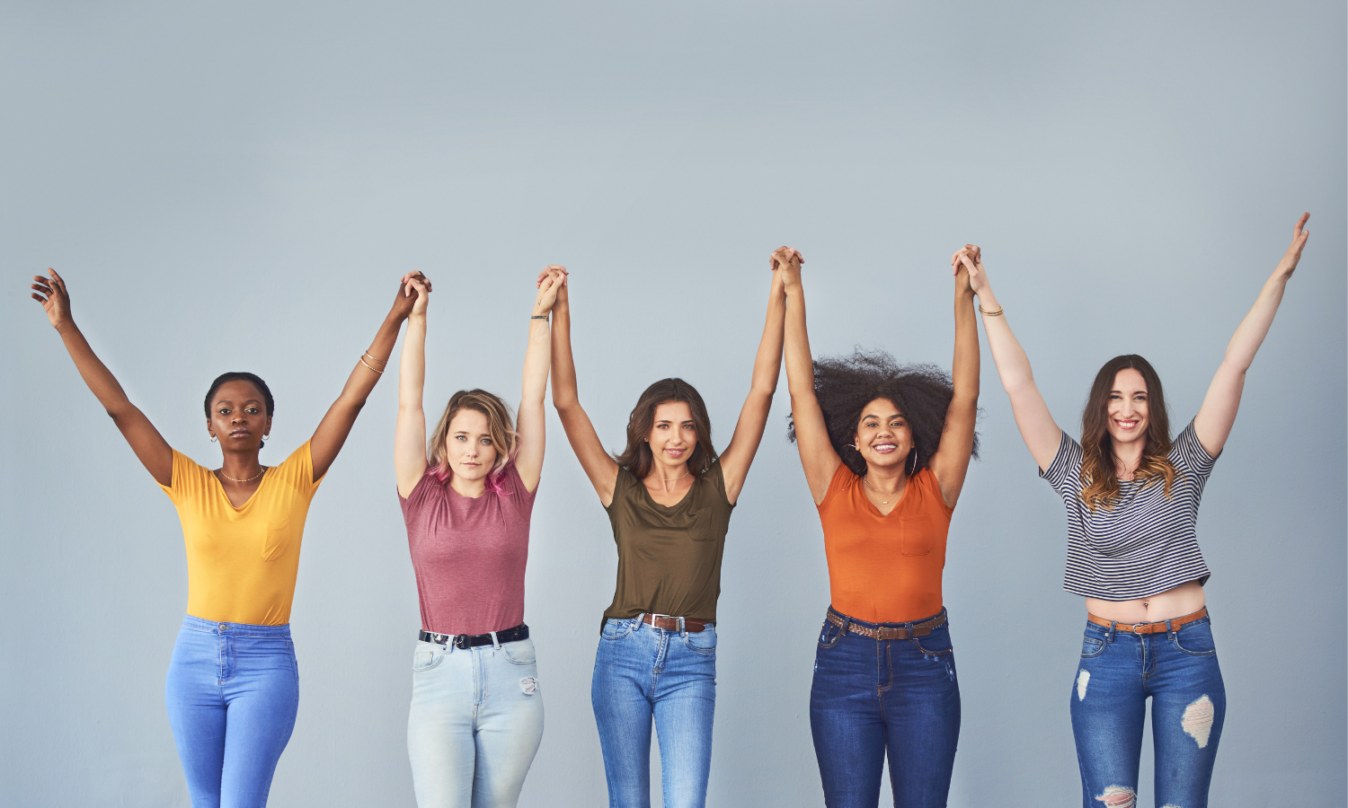 5 women hands joined raised above their heads in unity