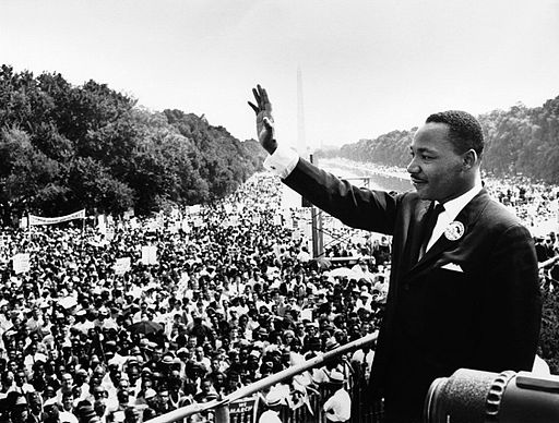 Dr. Martin Luther King, Jr. waves to a massive crowd from the steps of the Lincoln Memorial.