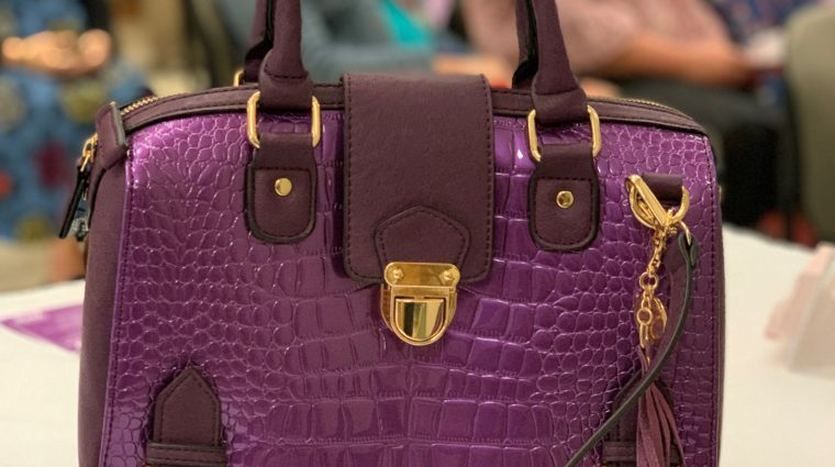 A close up of a purple purse in the foreground of a photo.