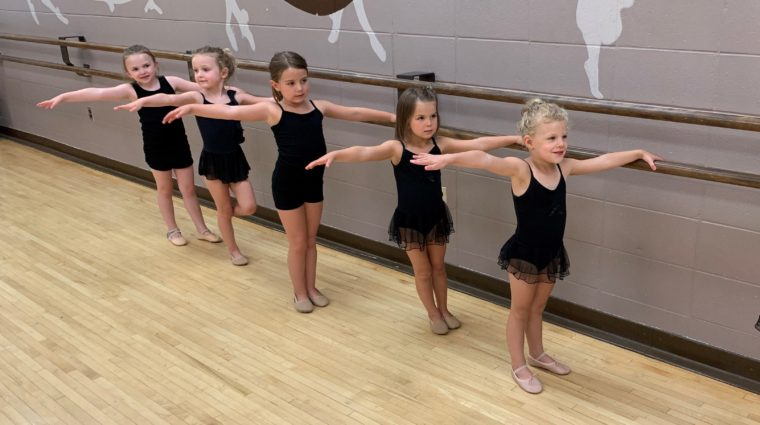 School age dancers stand at the ballet barre