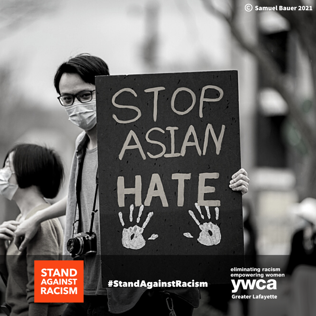 black and white photo of Asian American man holding a sign that says stop Asian hate