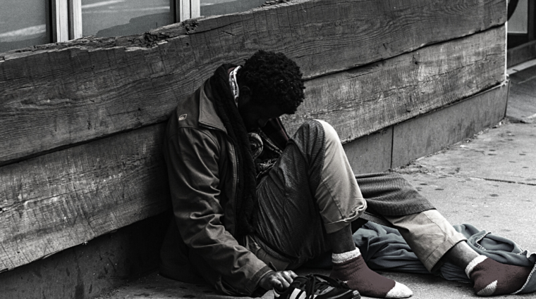 homeless black man on a sidewalk putting on his shoes, with the text stand against racism