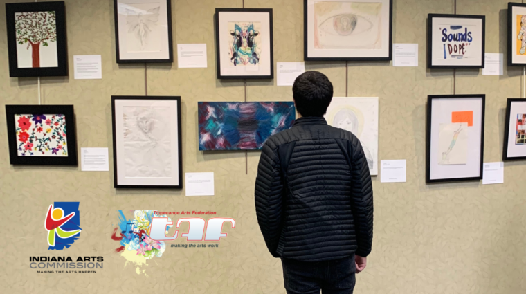 A person stands with their back to the camera, viewing a gallery wall full of framed art. Two logos are situated in the bottom left corner: Indiana Arts Commition and Tippecanoe Arts Federation.