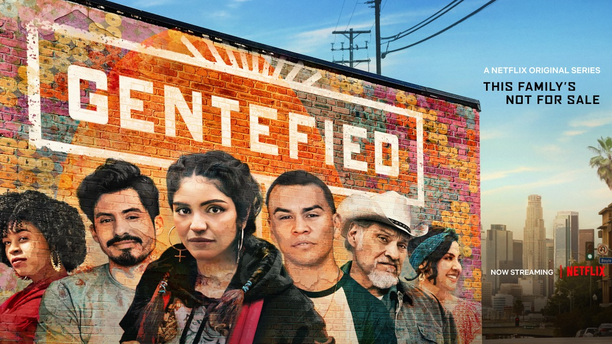 "Photo of a brick building with a mural of a Latinx family painted over the bricks. Reads ""Gentefied, a netflix original series. This familiy's not for sale"""
