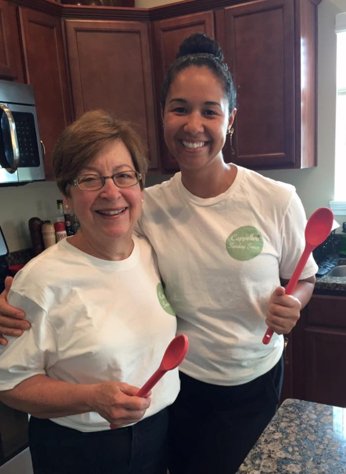 Betty (left) and Taylor (right) posing in the kitchen holding red ladles.